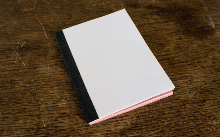 a softcover notebook with white cover and pink paper on the inside